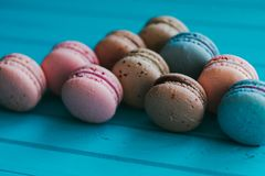 Multicolored macarons or macaroons on a turquoise wooden background, almond cookies in pastel tones.  Stock Photography