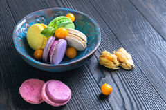 Multicolored macaroon cookies in a blue ceramic bowl Royalty Free Stock Images
