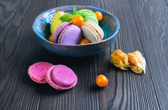 Multicolored macaroon cookies in a blue ceramic bowl Stock Photos