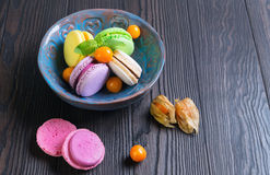 Multicolored macaroon cookies in a blue ceramic bowl Royalty Free Stock Photography