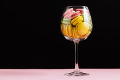 Multicolored macaroon in wine glass on a black and pink background. Author's processing, selective focus, film effect. Multicolored macaroon in wine glass on a Stock Photos