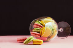 Multicolored macaroon in wine glass on a black and pink background. The author's processing, space for text. Stock Images
