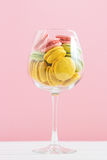 Multicolored macaroon in wine glass on a white and pink background. Author's processing, selective focus, film effect. Multicolored macaroon in wine glass on a Stock Image