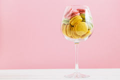 Multicolored macaroon in wine glass on a white and pink background. The author's processing, space for text. Macaroon in a wine glass on a white and pink Royalty Free Stock Image