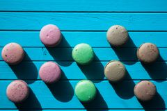 Multicolored macaroons or almond cookies lie on a wooden turquoise background in checkerboard pattern close-up, copy. Space Stock Photos