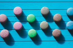 Multicolored macaroons or almond cookies lie on a wooden turquoise background in checkerboard pattern.  Stock Images