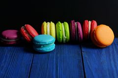 Multicolored macaroons on a dark blue wooden background.Low key Royalty Free Stock Photo