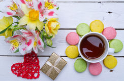 Multicolored macaroons, flowers, a gift and a cup of hot tea on Royalty Free Stock Images