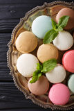 Multicolored macaroons and fresh mint closeup on a platter. Vert. Ical view from above royalty free stock image