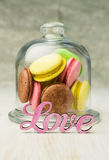 Multicolored macaroons in a glass bell jar Stock Photography