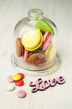Multicolored macaroons in a glass bell jar Royalty Free Stock Photo