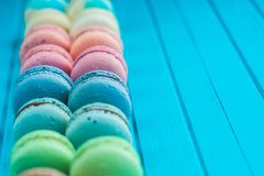 Multicolored macaroons lie in a row on a turquoise wooden background.  Royalty Free Stock Images