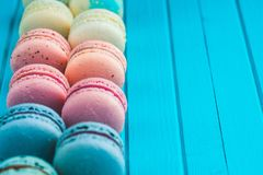 Multicolored macaroons lie in a row on a turquoise wooden background, copy space.  Royalty Free Stock Photography