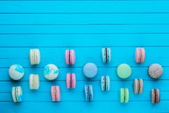 Multicolored macaroons or macaron lie in staggered order on a blue wooden background, copy space.  Royalty Free Stock Images