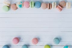 Multicolored macaroons or macaron on a white wooden background, almond cookies on a white desk, copy space. Multicolored macaroons or macaron on a white wooden Royalty Free Stock Photography