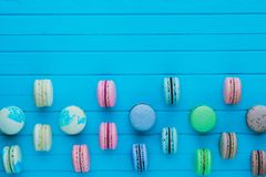 Multicolored macaroons or macarons in pastel colors lie in staggered order on a blue wooden background, copy space.  Stock Image