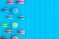 Multicolored macaroons or macarons in pastel colors lie in staggered order on a blue wooden background on the left, copy. Space Royalty Free Stock Photography