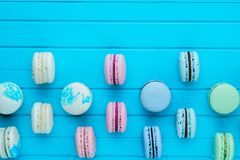 Multicolored macaroons or macarons in pastel colors lie in staggered order on a turquoise wooden background, copy space.  Royalty Free Stock Images