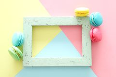 Multicolored macaroons on pastel geometric background and vintage empty frame. Multicolored macaroons on pastel geometric background and vintage empty frame royalty free stock images