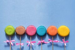 Multicolored macaroons on a stick with a bow lie in a row on a blue background.Copy space. French cookies