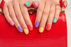 Multicolored manicure and expensive red handbag. Royalty Free Stock Photo