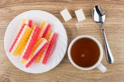 Multicolored marmalade, cup of tea, sugar and teaspoon on wooden Royalty Free Stock Photography