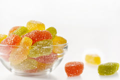 Multicolored marmalade sweets. In a glass plate on a white background, three sweets lie on a table Stock Photo