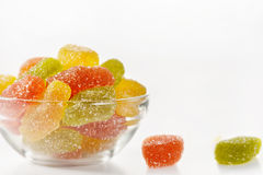 Multicolored marmalade sweets. In a glass plate on a white background, two sweets lie on a table Royalty Free Stock Photography
