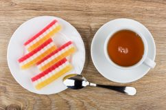 Multicolored marmalade in white plate, cup of tea and teaspoon. On wooden table. Top view Royalty Free Stock Images