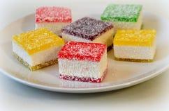 Multicolored marmelade in stukken op een witte plaat wordt gesneden die Stock Afbeelding