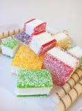 Multicolored marmelade in stukken op een witte plaat wordt gesneden die Stock Foto's