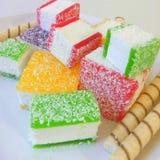 Multicolored marmelade in stukken op een witte plaat wordt gesneden die Royalty-vrije Stock Afbeeldingen