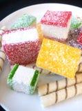 Multicolored marmelade in stukken op een witte plaat wordt gesneden die Stock Fotografie