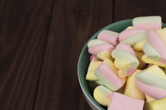 Multicolored marshmallows. Into a bowl on dark wooden background Royalty Free Stock Photos
