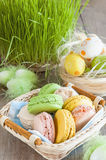 Multicolored meringues macaroons in a wicker basket of Easter eggs on a grass background for Easter stock photos