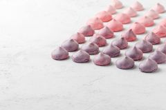 Multicolored meringues in purple-pink colors on a white table. Stock Photos