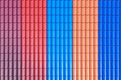 Multicolored, metal sheets of decorative siding. Multicolored, metallic sheets of undulating decorative siding Royalty Free Stock Image