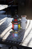 Multicolored moroccan lamp on table. With aerly morning sunlight at roof terras at riad in Maroc Royalty Free Stock Image