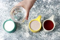 Multicolored mugs with drinks and female hand on a gray background, top view royalty free stock photos