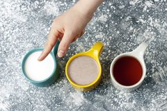 Multicolored mugs with hot drinks and female hand on a gray background, top view royalty free stock images
