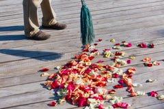 Multicolored nam bloemblaadjes worden geveegd met een bezem na weddin toe royalty-vrije stock afbeeldingen