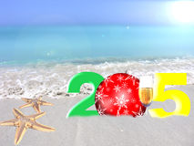 Multicolored New Year 2015. Happy new year 2015.Greeting card with Christmas red ball and a glass of champagne  on a tropical sea background Royalty Free Stock Photography