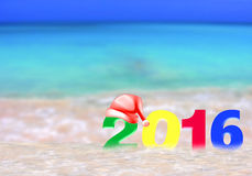 Multicolored New Year 2016. Happy new year 2016. Greeting card with numbers 2016 red hat of Santa Claus on a tropical background. The concept of the new year on Royalty Free Stock Photo