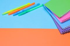 Multicolored notebooks and pens. stationery. school supplies on a blue and orange background. royalty free stock image