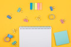 Colored art hobby set. Multicolored office supplies and blank notepad  laying on yellow background top view. Creative set for hobby Royalty Free Stock Photos