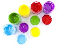 Multicolored paint in open banks. On a white background Royalty Free Stock Photography