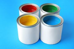 Multicolored paint in tin cans. On color background royalty free stock photos
