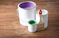 Multicolored paint in tin cans. On wooden background stock image