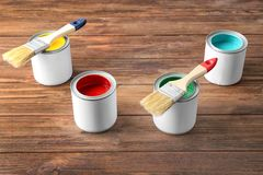 Multicolored paint in tin cans. On wooden background stock photos