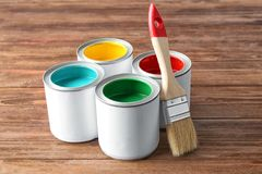 Multicolored paint in tin cans. On wooden background royalty free stock photos